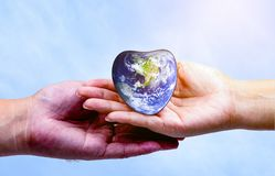 Hand man holding heart earth and listening to heart stock image