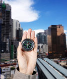 The hand of a man holding a magnetic compass over a city buildings Stock Photography