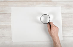 Hand of man holding the magnifying glass over white paper lying on wooden surface Royalty Free Stock Photos