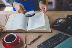 Magnifying. A hand of man holding magnifying text book on table with accessories and coffee royalty free stock image