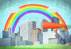 Hand of man holding orange paper trumpet against illustrated background Royalty Free Stock Image