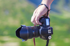 Hand of a man holding professional digital camera on blurred gre Royalty Free Stock Images