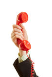 The hand of a man holding a red telephone Stock Images