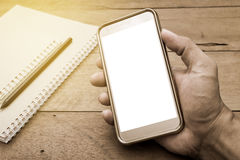 Hand man holding smart phone mobile white screen on office table. Hand of young man holding smart phone mobile white screen with notepad and pencil on office Stock Photo