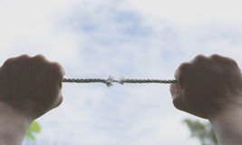 Hand of man holding on to the rope it`s almost absent under the. Sky Stock Photo