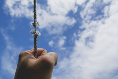 Hand of man holding on to the rope it`s almost absent under the. Sky Royalty Free Stock Photography