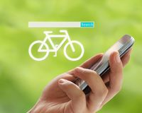 Hand of man holds a smartphone in search box and bicycle symbol Stock Photos