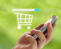 Hand of man holds a smartphone in search box and shopping cart s Royalty Free Stock Photo