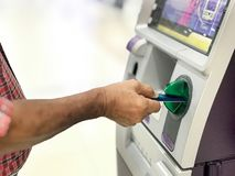 Hand of man insert card into ATM machine for withdraw money with blurry background. Stock Photography