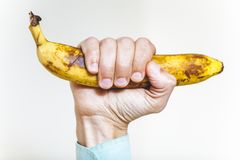 Ripe banana in hand man on white background stock photos