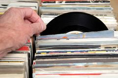 Hand of a man looking at vinyl 7& x22; single 45 rpm records for sale at a retro record fair.  Stock Photo