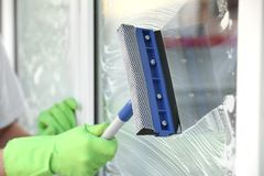 Hand of man with mop washing window. Outdoors Stock Photography