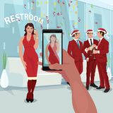 Making photo of girl at office New Year party. Hand of man at office party makes photo of beautiful girl in red dress on smartphone. Employees celebrate New Year Stock Photos