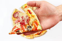 Hand man with a piece of flavored pizza closeup Stock Photos