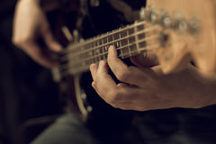 Hand of a man playing bass guitar Stock Photography