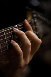 The hand of man playing guitar. Hand of a man playing guitar closeup in dark colors Royalty Free Stock Photography
