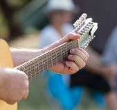 Hand man playing the guitar. In the park in nature Royalty Free Stock Photos