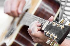 Hand man playing the guitar. In the park in nature Stock Photos