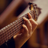 The hand of man playing guitar. Hand on the strings of the guitar closeup Royalty Free Stock Photography