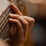 The hand of man playing guitar. Hand on the strings of the guitar closeup Royalty Free Stock Photos