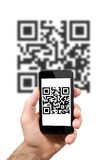 Hand of man is in possession of smartphones that displays a qr c Royalty Free Stock Image