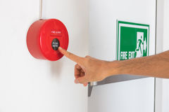 The hand of man is press fire alarm on the wall next to the door Stock Photo