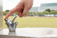 Hand man push button of drinking water faucet at park Royalty Free Stock Photo