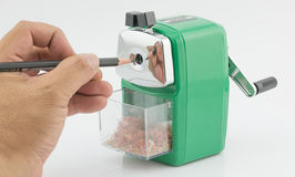 Hand man put pencil to green sharpener pencil. Stock Photo