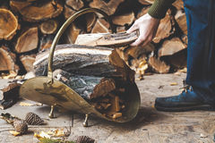 Hand man puts piece of wood in metal woodpile. Hand man puts a piece of wood into the copper drovnitsu against the backdrop of stacked firewood royalty free stock photography