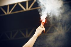 The hand of a man is raised in the air with a burning red flame fire royalty free stock image