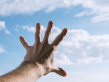 Hand of a man reaching to sky. Hand of a man reaching to towards sky. Color toned image. Selective focus Royalty Free Stock Photo