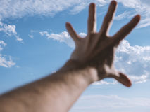 Hand of a man reaching to towards sky. Color toned image. Selective focus Royalty Free Stock Photo