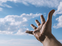 Hand of a man reaching to towards sky. Color toned image. Selective focus Stock Photos