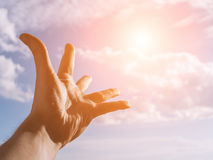 Hand of a man reaching to towards sky. Color toned image. Selective focus Royalty Free Stock Photography