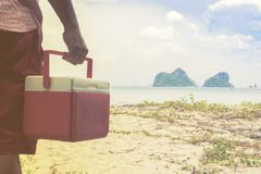 Hand  of man red Ice box  with background the beach and island view. 1 Stock Photos