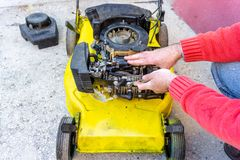 Hand of man repairing old grass cutter with tools on cement floor. Repairing lawn mower engine.  royalty free stock photos