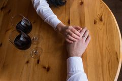 The hand of a man with a ring stretches to the woman`s hand. Two glasses with red wine. Romantic dinner, a date. The hand of coupl. E in love with wedding rings Royalty Free Stock Images