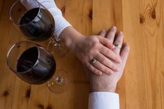 The hand of a man with a ring stretches to the woman`s hand. Two glasses with red wine. Romantic dinner, a date. The hand of couple in love with wedding rings Royalty Free Stock Images