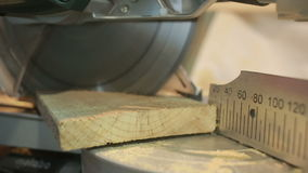 Hand man sawed wooden board using a miter saw with laser stock footage