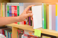 Hand of man selecting a book from book shelf. Stock Image