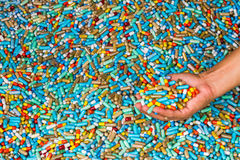 Hand of man show many colorful medicines expire on cement floor Stock Photo