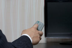 Hand man in a suit with a remote control to the TV Stock Photos