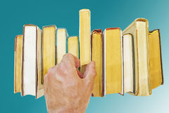 Hand of man takes book from shelf  Royalty Free Stock Images