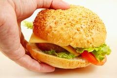 Hand man takes a flavored hamburger closeup Royalty Free Stock Photo