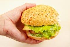 Hand man with a tasty hamburger closeup Royalty Free Stock Image
