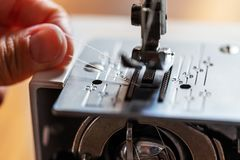 Hand of a man is threading a thread at the presser foot. Of his sewing machine royalty free stock photos