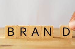 Hand man try to complete the Brand word on wooden cube, Brand concept royalty free stock photos