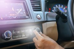 Hand of man turning on car air conditioning system,Button on dashboard in car. Panel royalty free stock photo
