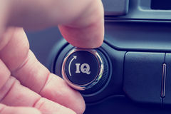 Hand of a man turning up a dial with the word IQ and an arrow Stock Photography