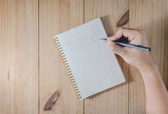 Hand of man use pencil writing `TO DO LIST` on white notebook on wooden table. Hand of man use pencil writing `TO DO LIST` on white notebook Royalty Free Stock Photo